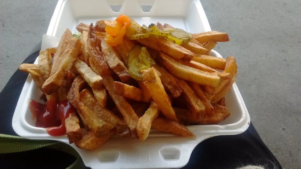 french fries in styrofoam container, topped with hot peppers and a corner with ketchup