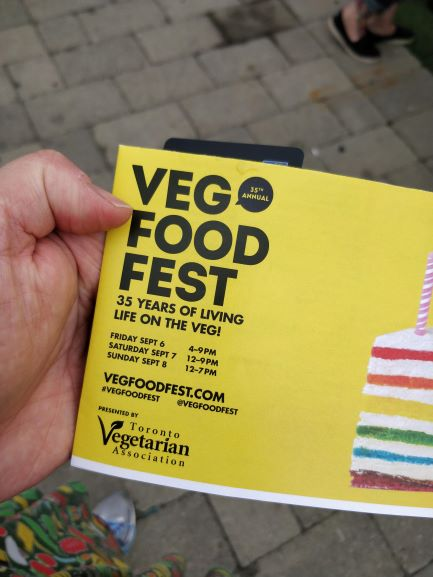 A picture of my hand holding a Veg Food Fest brochure.